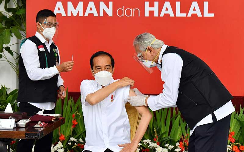 Presiden Joko Widodo (tengah) bersiap disuntik dosis pertama vaksin Covid-19 produksi Sinovac oleh vaksinator Wakil Ketua Dokter Kepresidenan Abdul Mutalib (kanan) di beranda Istana Merdeka, Jakarta, Rabu (13/1/2021). Penyuntikan perdana vaksin Covid-19 ke Presiden Joko Widodo tersebut menandai dimulainya program vaksinasi di Indonesia. ANTARA FOTO/HO - Setpres/Agus Suparto