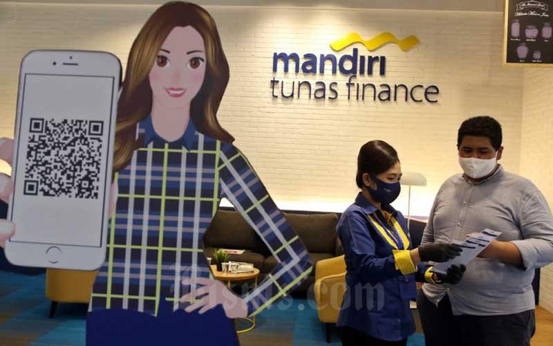 Karyawan melayani nasabah di Kantor Mandiri Tunas Finance, Jakarta, Jumat (25/9/2020). Bisnis - Eusebio Chrysnamurti