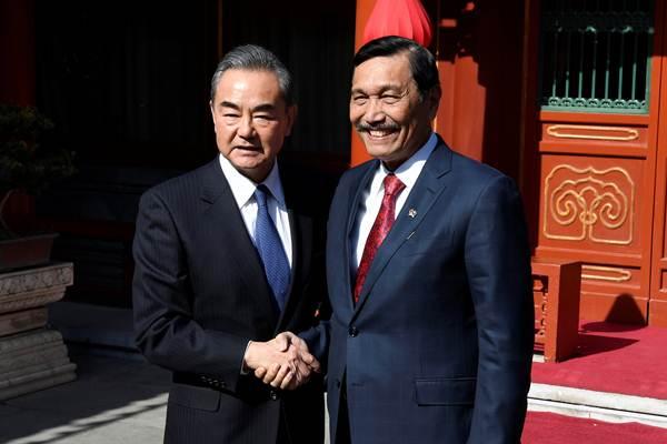 Menteri Koordinator Kemaritiman Luhut Pandjaitan (kanan) berjabat tangan dengan Menteri Luar Negeri China Wang Yi sebelum pertemuan di Wisma Negara Diaoyutai di Beijing, China, Rabu (24/10/2018). - Reuters/Daisuke Suzuki