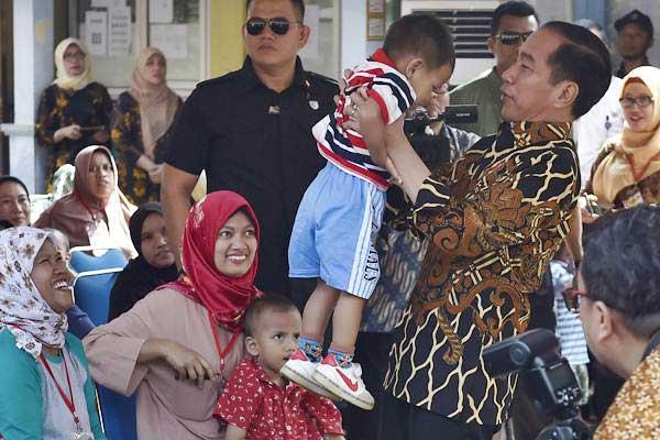 Presiden Joko Widodo menggendong balita saat mengunjungi Posyandu Kenanga II bersama Presiden Bank Dunia Jim Yong Kim di Desa Tangkil, Caringin, Kabupaten Bogor, Jawa Barat, Rabu (4/7/2018). - ANTARA/Puspa Perwitasari