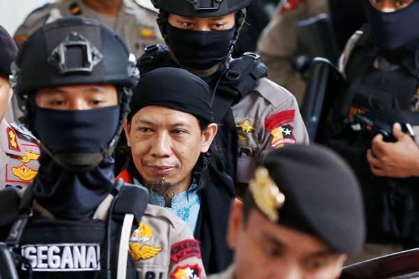 Terdakwa kasus dugaan terorisme Oman Rochman alias Aman Abdurrahman dikawal polisi seusai menjalani sidang pembacaan vonis di Pengadilan Negeri Jakarta Selatan, Jakarta, Jumat (22/6/2018). Majelis hakim memvonis Aman Abdurrahman dengan hukuman mati. - Reuters/Darren Whiteside