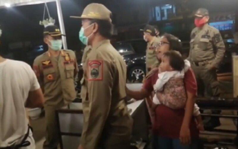 Salah satu pedagang (perempuan menggendong anak) terlihat protes jam malam PPKM Sukoharjo ke petugas. - Instagram/@infocegatansukoharjo.