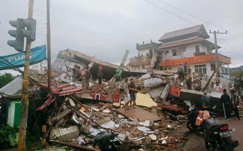 Warga memeriksa bangunan rusak akibat gempa di Mamuju, Sulawesi Barat, Jumat (15/1/2021) pagi. - Istimewa/AP/Rudy Akdyaksyah