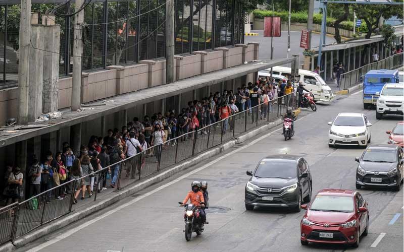 Penumpang mengantri untuk naik kereta Mass Rapid Transit (MRT) menjelang jam malam yang diberlakukan karena corona virus di Mandaluyong City, Metro Manila, Filipina, Senin (16/3/2020). Bloomberg - Veejay Villafranca