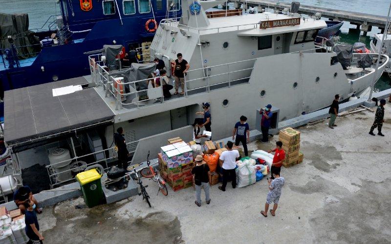 Sejumlah relawan menurunkan bantuan logistik dari atas kapal di Pangkalan Angkatan Laut (Lanal) Kabupaten Mamuju, Sulawesi Barat, Sabtu (16/1/2021). Bantuan logistik tersebut untuk warga terdampak bencana gempa bumi di Sulawesi Barat.  - ANTARA