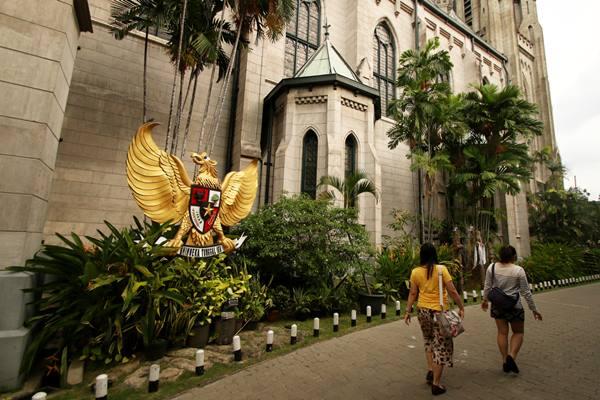 Umat Kristiani melintas di area Gereja Katedral, Jakarta, Jumat (23/6). Gereja Katedral mengubah jadwal misa Minggu pagi yang bertepatan dengan Hari Raya Idul Fitri menjadi lebih siang guna menghormati umat Muslim yang akan melaksanakan Salat Idulfitri. ANTARA FOTO - Rivan Awal Lingga