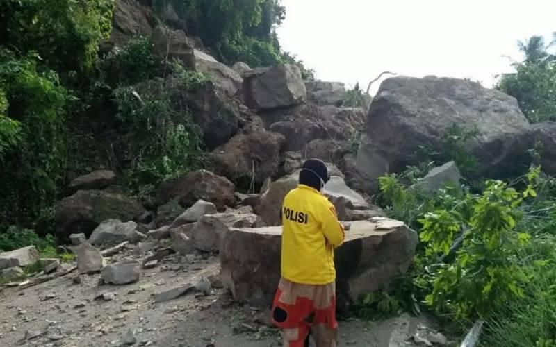 Seorang relawan yang tertahan di Jalan Poros Majene, Kabupaten Sulawesi Barat melihat lebih dekat material longsor yang menutupi badan jalan, Senin (18/1/2021). - Antara