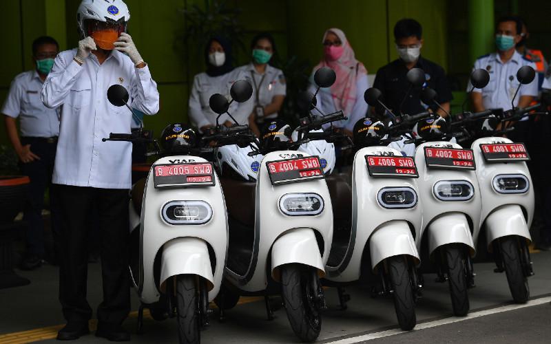 Menteri Perhubungan Budi Karya Sumadi (kiri) bersiap mengendarai motor listrik saat diluncurkan sebagai kendaraan dinas Kementerian Perhubungan di Stasiun Gambir, Jakarta, Rabu (16/12/2020).  - ANTARA FOTO