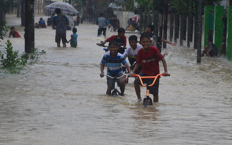 Sejumlah bocah bermain sepeda di jalan yang tergenang banjir di Desa Kesambi, Mejobo, Kudus, Jawa Tengah, Selasa (19/1/2021). Akibat intensitas hujan yang tinggi sejak dua hari terakhir serta meluapnya sejumlah sungai di wilayah setempat menyebabkan ratusan rumah dan jalan utama terdampak banjir dengan ketinggian 30-80 centimeter.  - Antara/Yusuf Nugroho.