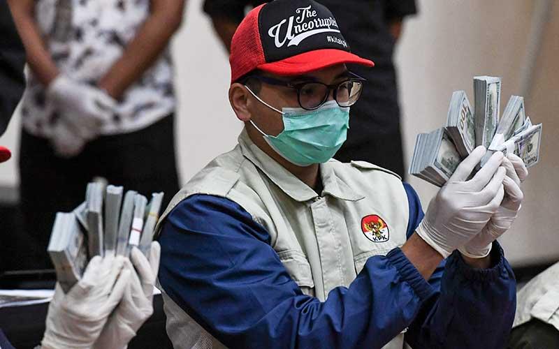 Penyidik KPK menunjukan barang bukti uang tunai saat konferensi pers terkait Operasi Tangkap Tangan (OTT) tindak pidana korupsi pada program bantuan sosial di Kementerian Sosial untuk penanganan Covid-19 senilai Ro14,5 miliar di Gedung KPK, Jakarta, Minggu (6/12/2020) dini hari. ANTARA FOTO/Hafidz Mubarak A - rwa