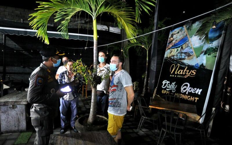 Petugas Satpol PP Badung meminta wisatawan mancanegara pengunjung lokasi usaha yang melewati batas jam operasional untuk membubarkan diri saat sidak penerapan Pemberlakuan Pembatasan Kegiatan Masyarakat (PPKM) di kawasan Canggu, Badung, Bali, Senin (11/1/2021). Sidak tersebut dilakukan untuk memantau dan menertibkan berbagai lokasi kegiatan usaha saat hari pertama penerapan kebijakan PPKM di Bali. - Antara/Fikri Yusuf.