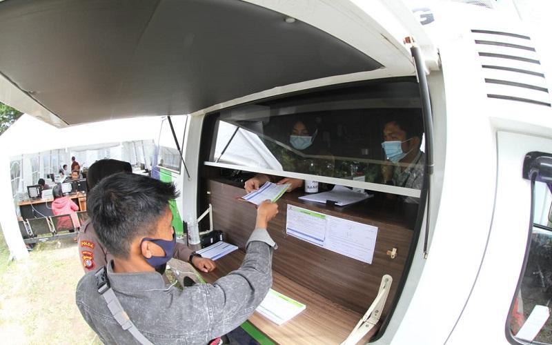 Nasabah melakukan transaksi perbankan di Bank Sulawesi Selatan dan Barat di Mamuju Rabu (20/1). Hari kelima pasca gempa aktivitas perbankan mulai buka meski masih dalam keterbatasan dan menggunakan mobil kas keliling dengan tenda darurat - Paulus Tandi Bone