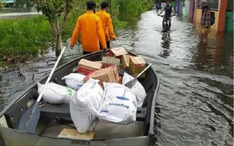 Para anggota BPBD Kota Banjarmasin, Kalsel, Rabu (20/1/2021) menggunakan perahu saat mengantar bantuan untuk warga terdampak banjir. - Antara