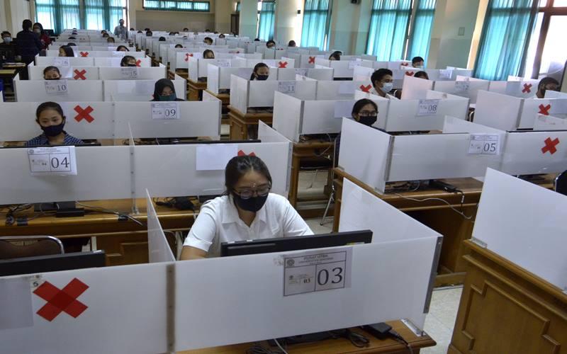 Sejumlah peserta mengikuti pelaksanaan Ujian Tulis Berbasis Komputer (UTBK) Seleksi Bersama Masuk Perguruan Tinggi Negeri (SBMPTN) 2020 di Universitas Udayana, Denpasar, Bali, Minggu (5/7/2020). Sebanyak 5.239 orang peserta mengikuti UTBK SBMPTN 2020 di Universitas Udayana yang dilaksanakan dengan menerapkan berbagai protokol kesehatan untuk mencegah penyebaran pandemi COVID-19. ANTARA FOTO - Fikri Yusuf