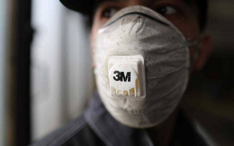 Seorang pekerja mengenakan masker buatan 3M Co. ketika membersihkan bus penumpang di sebuah terminal di Moskow, Rusia, Kamis (19/3/2020). - Bloomberg/Andrey Rudakov