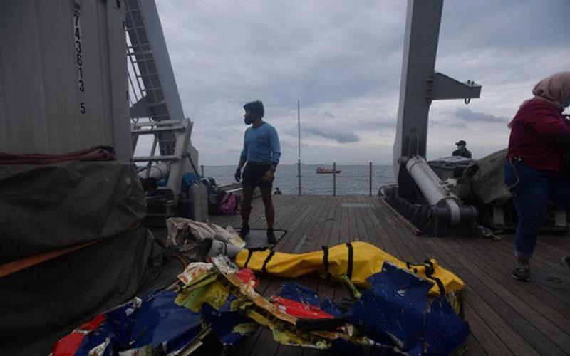 Prajurit Kopaska TNI AL berdiri di dekat kantong berisi jenazah dan serpihan dari pesawat Sriwijaya Air SJ182 yang dievakuasi ke atas KRI Rigel-933 di perairan Kepulauan Seribu, Jakarta, Minggu (10/1/2021)./Antara - Sigid Kurniawan
