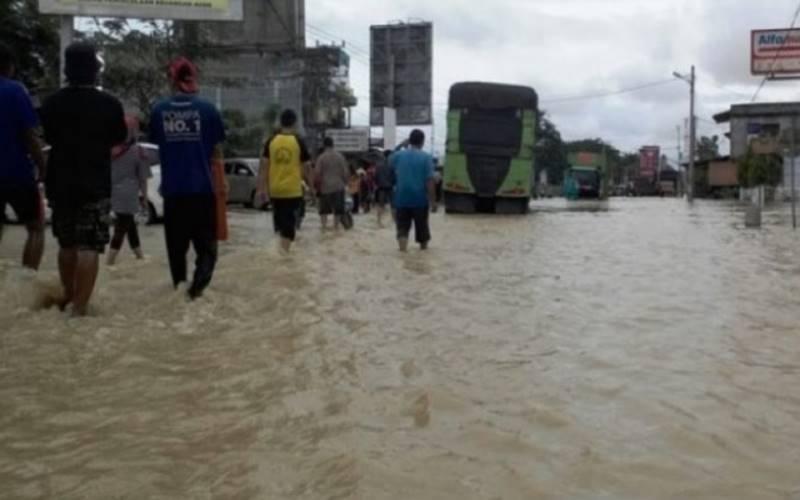 Dokumentasi - Warga mengarungi banjir di jalan lintas nasional Medan- Banda Aceh tepatnya di Kota Lhoksukon, Aceh Utara, Minggu (6/12/2020). - Antara