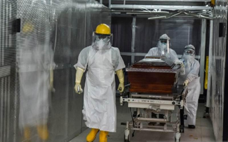 Ilustrasi - Sejumlah tenaga kesehatan membawa peti berisi jenazah di halaman RSUD Arifin Achmad, Kota Pekanbaru, Riau, Kamis (24/9/2020). - Antara/FB Anggoro