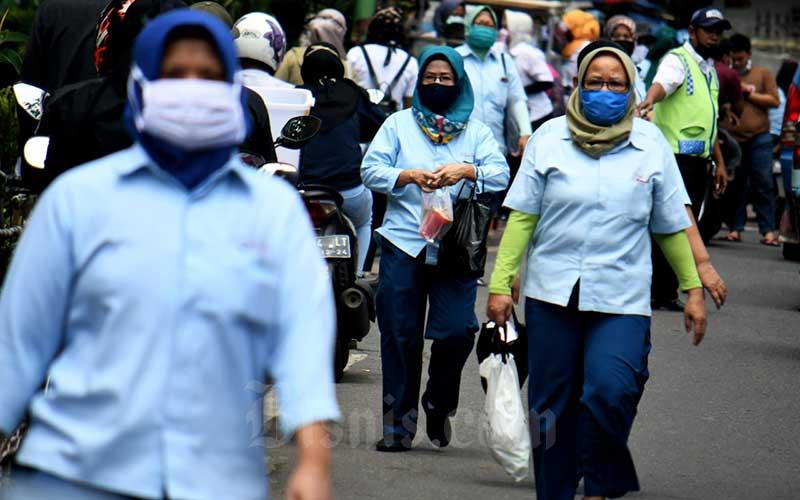 Pekerja pabrik pulang seusai bekerja di salah satu pabrik makanan di Jakarta, Sabtu (11/4/2020). Bisnis - Abdurachman