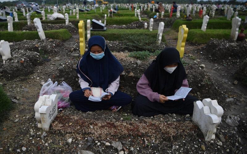 Warga berdoa saat melakukan ziarah di kuburan khusus kasus Covid-19 di TPU Keputih di Surabaya, Jawa Timur, Kamis (21/1/2021). Berdasarkan data Satuan Tugas Penanganan Covid-19 pada Kamis (21/1), jumlah kasus terkonfirmasi positif Covid-19 bertambah 11.703 sehingga total positif menjadi 951.651 dan kasus pasien Covid-19 yang meninggal dunia bertambah 346 orang, sehingga total menjadi 27.203 orang. - Antara/Zabur Karuru.
