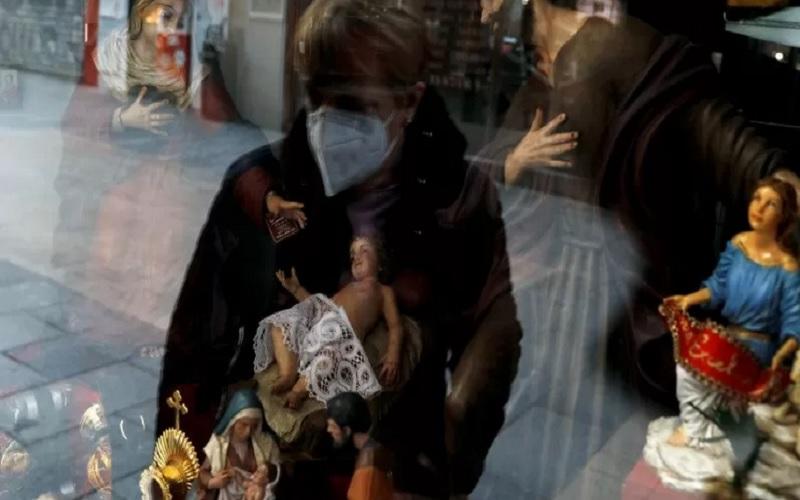 Seorang perempuan memakai masker pelindung melihat patung keagamaan di sebuah toko, di tengah penyebaran penyakit Covid-19 di Madrid, Spanyol, Rabu (9/12/2020). - Antara/Reuters\r\n