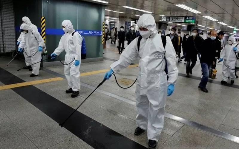 Para karyawan dari sebuah perusahaan layanan desinfeksi membersihkan stasiun subway di tengah ketakutan Virus Corona di Seoul, Korea Selatan, Rabu (11/3/2020). - Antara