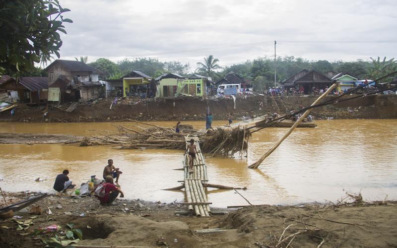 Warga menyeberang sungai menggunakan jembatan darurat akibat jembatan gantung di Desa Alat putus akibat banjir bandang di Kabupaten Hulu Sungai Tengah, Kalimantan Selatan, Rabu (20/1/2021).   - Antara