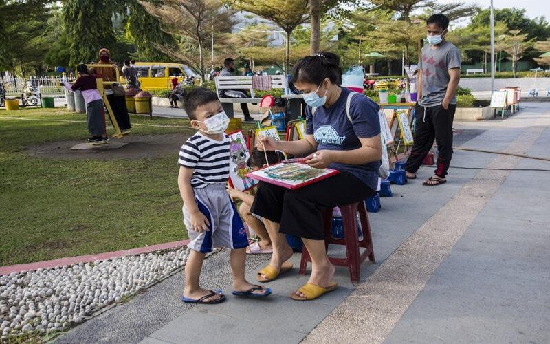 Sejumlah warga mengenakan masker saat bermain di Taman Tunjuk Ajar Melayu, Kota Pekanbaru, Provinsi Riau, Minggu (24/1/2021). Pemerintah Indonesia berupaya menekan penyebaran pandemi, salah satunya mengajak masyarakat selalu mengenakan masker, karena sejak awal tahun 2021 terjadi lonjakan kasus Covid-19 baru yang rata-rata mencapai 10.000 orang dalam sehari dengan total kasus akumulatif sudah lebih dari 977.474 orang berdasarkan data Satgas Covid-19. - Antara/FB Anggoro.