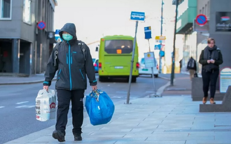 Seorang pria memakai masker membawa kantong belanja di sebuah jalan di Oslo, Norwegia, Jumat (13/3/2020), di tengah wabah Covid-19. - Antara/Reuters\r\n