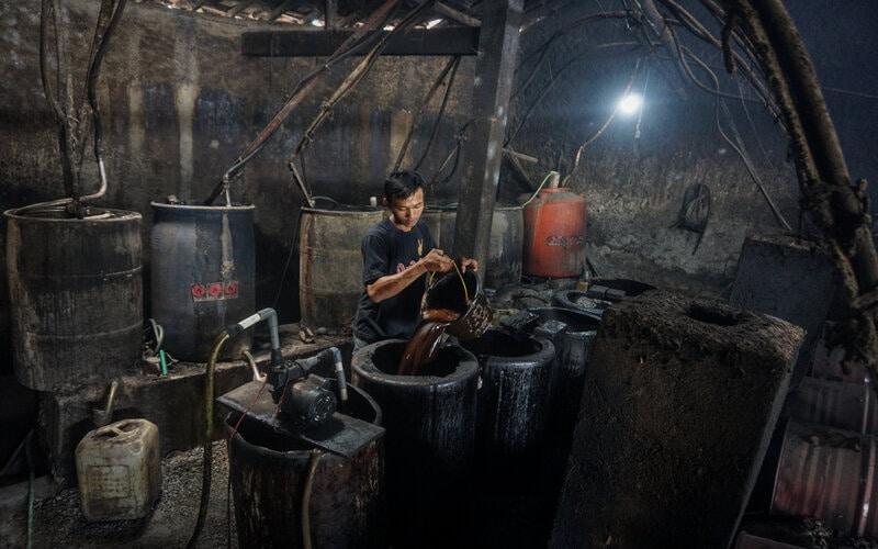 Pekerja menyelesaikan proses pembuatan etanol atau alkohol 90 persen dari fragmentasi tebu di Sentra Industri Alkohol, Bekonang, Sukoharjo, Jawa Tengah, Rabu (20/1/2021). Menurut perajin permintaan alkohol 90 persen untuk keperluan medis meningkat 100 persen selama Pandemi Covid-19. - Antara/Mohammad Ayudha.