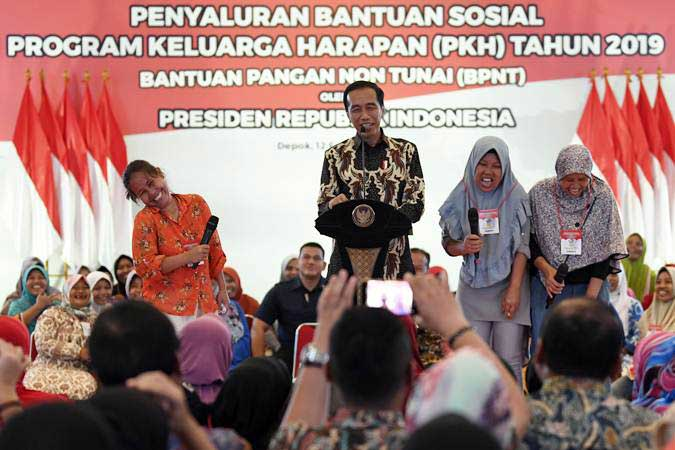 Presiden Joko Widodo (kedua kiri) berbincang dengan penerima Bantuan Sosial Program Keluarga Harapan (PKH) Tahun 2019 di Sukmajaya, Depok, Jawa Barat, Selasa (12/2/2019). - ANTARA FOTO/Puspa Perwitasari