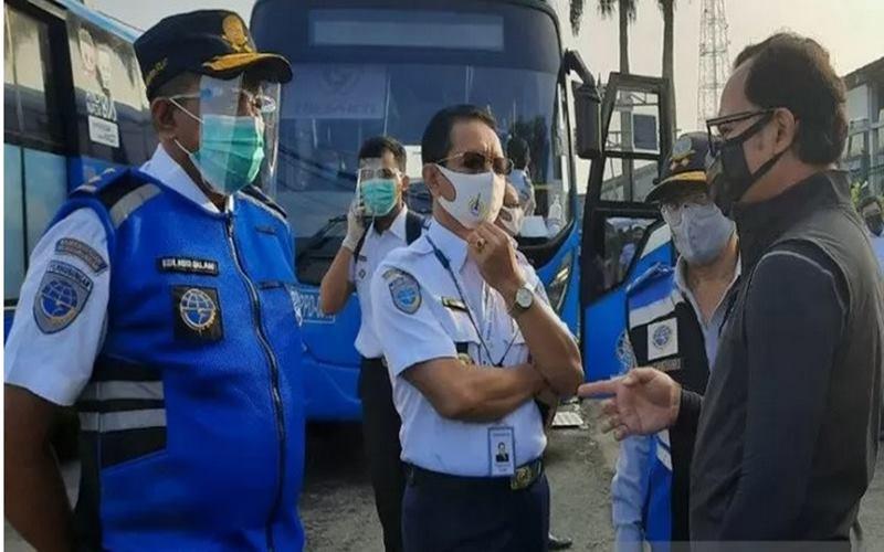 Direktur Utama Perum PPD, Pande Putu Yasa (tengah) berbincang dengan Wali Kota Bogor Bima Arya (kanan) di Bogor, Jawa Barat, Minggu (19/7/2020), terkait pengerahan bantuan bus untuk penumpang KRL di Stasiun Bogor menuju Jakarta. - Antara