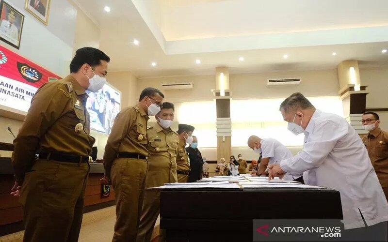 Gubernur Sulsel HM Nurdin Abdullah (dua kiri) menyaksikan proses penandatanganan MoU SPAM Mamminasata bersama kepala daerah di Makassar, Senin (25/1/2021). - Antara/Handout.