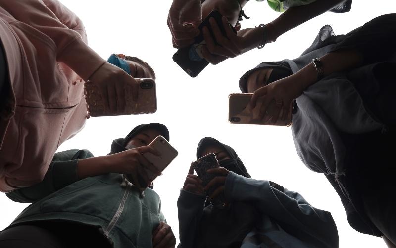 Sejumlah remaja menggunakan ponsel saat berkomunikasi di Medan, Sumatera Utara, Jumat (17/4/2020). - ANTARA FOTO/Septianda Perdana