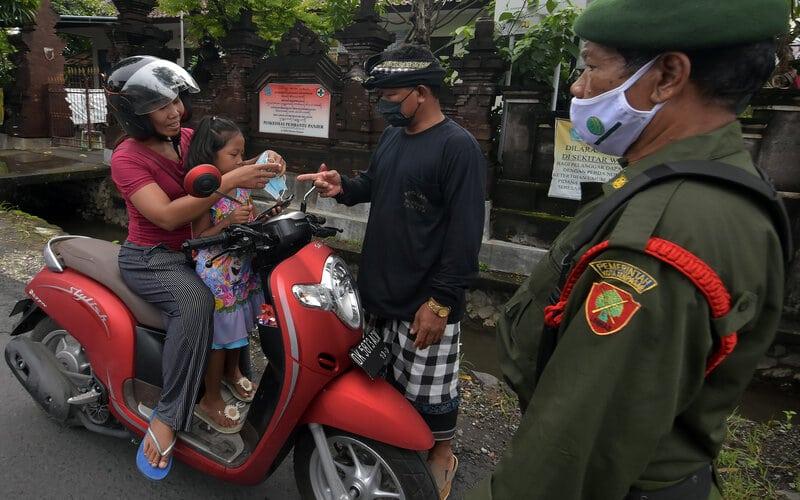 Pecalang dan petugas Linmas menegur pengendara sepeda motor yang tidak menerapkan protokol kesehatan dalam Pemberlakuan Pembatasan Kegiatan Masyarakat (PPKM) tingkat desa/kelurahan di Denpasar, Bali, Senin (18/1/2021). PPKM tingkat desa/kelurahan di Denpasar tersebut digelar pada 18 Januari hingga 18 Februari 2021 menyusul meningkatnya kasus positif Covid-19 di wilayah itu. - Antara/Nyoman Hendra Wibowo.