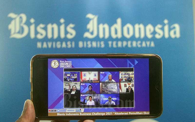 Layar menampilkan Menko Bidang Perekonomian Airlangga Hartarto (baris atas kanan), Ketua Dewan Komisioner OJK Wimboh Santoso (baris atas kedua kiri), Kepala Badan Kebijakan Fiskal Kementerian Keuangan Febrio Kacaribu (baris tengah kanan), Ketua Umum Apindo Hariyadi B. Sukamdani (baris tengah kedua kiri), Komisaris PT Jurnalindo Aksara Grafika (JAG) Budiarsa (baris atas kedua kanan)saat mengikuti Bisnis Indonesia Business Challenges 2021 di Jakarta, Selasa (26/1/2021). Bisnis - Arief Hermawan P