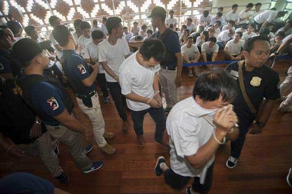 Polisi memeriksa warga negara China yang akan dideportasi ke negaranya di Bandara Ngurah Rai, Denpasar, Rabu (6/6/2018). - ANTARA/Nyoman Budhiana