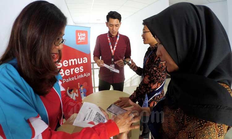 Petugas mensosialisasikan penggunaan QRIS dengan aplikasi layanan uang elektronik LinkAja di sela-sela kick off Pekan QRIS Nasional 2020 di kampus Universitas Pendidikan Indonesia, Bandung, Jawa Barat, Senin (9/3/2020). Bisnis - Rachman