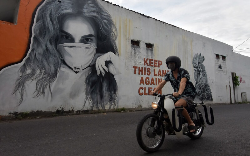Pengendara sepeda motor melintas di dekat mural bergambar perempuan menggunakan masker di Badung, Bali, Minggu (24/1/2021). Jumlah kasus positif Covid-19 di Bali meningkat saat Pemberlakuan Pembatasan Kegiatan Masyarakat (PPKM). - Antara/Nyoman Hendra Wibowo.