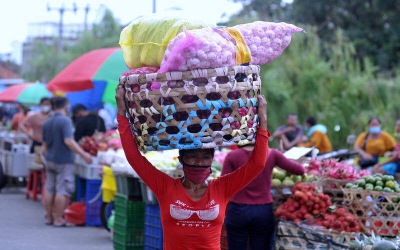 Seorang perempuan memikul barang di atas kepalanya di Pasar Badung, Denpasar, Bali, Selasa (26/1/2021). Pemerintah memperpanjang masa Pemberlakuan Pembatasan Kegiatan Masyarakat (PPKM) di Pulau Jawa dan Bali selama dua pekan hingga 8 Februari mendatang untuk menekan penyebaran Covid-19. - Antara/Fikri Yusuf.