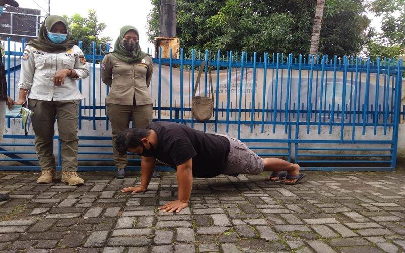 Pelanggar protokol kesehatan diberi sanksi push up oleh petugas Satpol PP Semarang. - Bisnis/Alif N.
