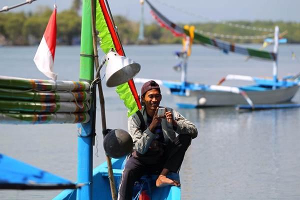 Nelayan mengakses aplikasi di Pantai Perancak Jembrana, Bali. - JIBI