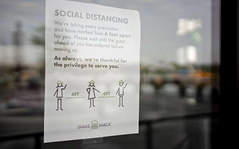 Ilustrasi - Pengumuman social distancing di tempel pada restoran Shake Shack Inc. di The Wharf Washington, DC, Amerika Serikat, Selasa (7/4/2020). - Bloomberg/Andrew Harrer