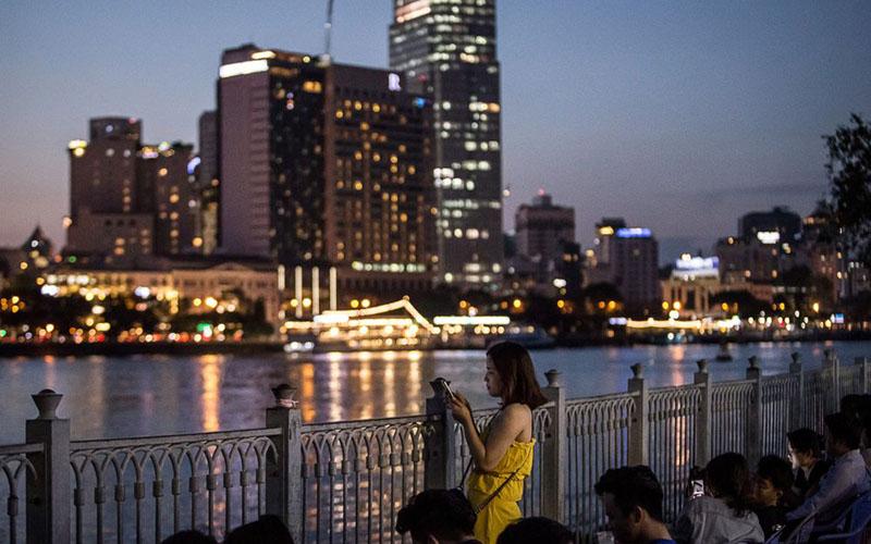 Warga menikmati keindahan malam di tepi Sungai Saigon di Ho Chi Minh City, Vietnam, berlatar belakang kilauan properti vertikal./Bloomberg - Yen Duong