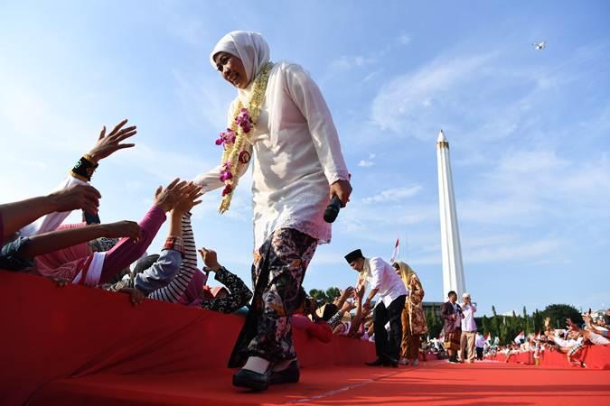 Gubernur Jawa Timur Khofifah Indar Parawansa (kiri) bersama Wakil Gubernur Jawa Timur Emil Elestianto Dardak (kedua kiri) menyapa warga di kawasan Tugu Pahlawan, Surabaya, Jawa Timur, Kamis (14/2/2019). - Antara/Zabur Karuru