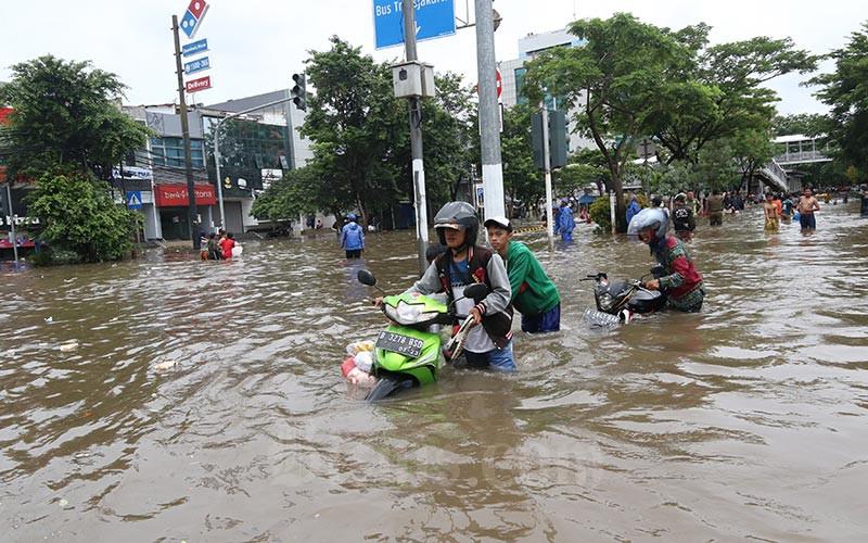 Warga melintasi banjir yang menggenangi Jalan Panjang, Kebon Jeruk, Jakarta, Selasa (25/2/2020). Bisnis - Eusebio Chrysnamurti