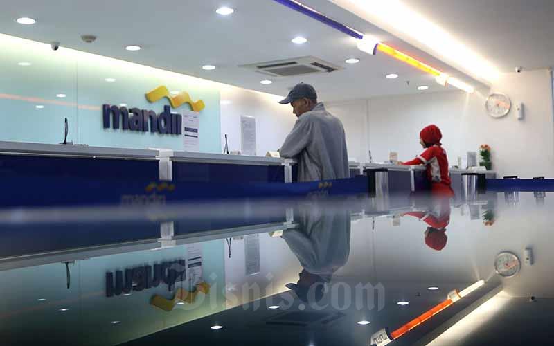 Karyawan melayani nasabah di salah satu kantor cabang milik PT Bank Mandiri (Persero) Tbk. di Jakarta, Kamis (4/7). Bisnis - Nurul Hidayat