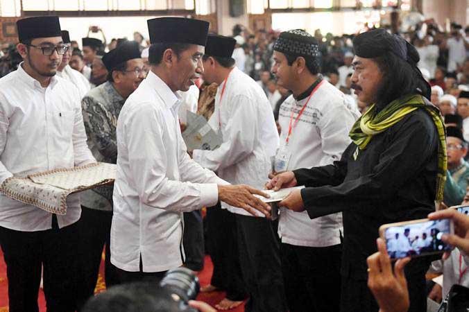 Presiden Joko Widodo (kedua kiri) memberikan sertifikat tanah wakaf kepada warga di Masjid Raya Bani Umar, Tangerang Selatan, Jumat (22/2/2019). - ANTARA/Akbar Nugroho Gumay