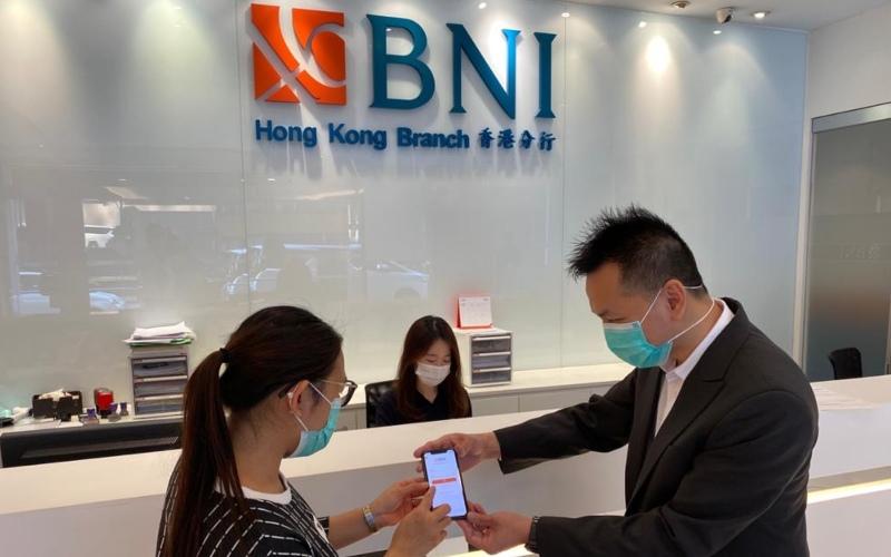 Pegawai sedang membantu nasabah untuk melakukan aktivasi BNI Mobile Banking di Kantor Cabang BNI Hongkong - dokumen BNI