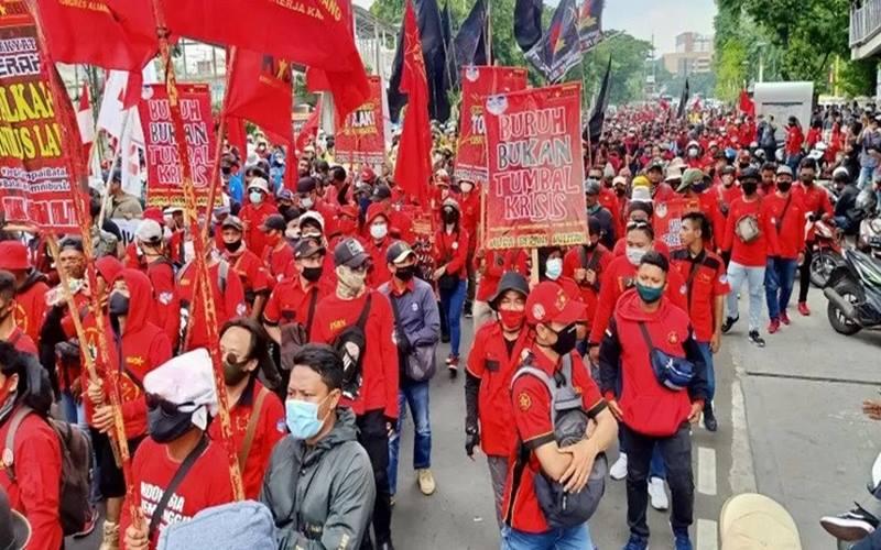 Massa buruh berjalan kaki di Jalan Salemba Raya, Jakarta Pusat, menuju kawasan Monas dalam rangkaian aksi penolakan Undang-Undang Cipta Kerja, Selasa (20/10/2020). - Antara